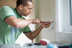 young adult latino man replacing electrical outletの写真素材 [FYI02286884]