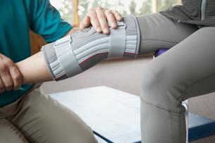 therapist adjusting knee brace on patientの写真素材 [FYI02286898]