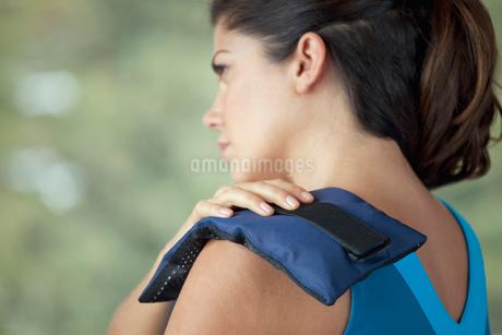 woman applying heat to sore muscleの写真素材 [FYI02286956]