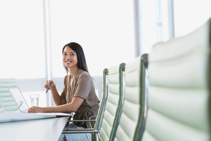 Young businesswoman sitting with laptop at conference tableの写真素材 [FYI02286961]
