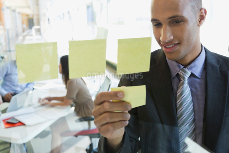 Businessman putting sticky notes on glass wallの写真素材 [FYI02286967]