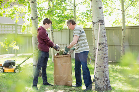 father and son doing yardwork togetherの写真素材 [FYI02287042]