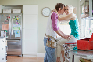 mid adult couple being affectionate in the kitchenの写真素材 [FYI02287046]