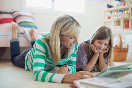 Happy mother and daughter looking at photo album while lying on floorの写真素材 [FYI02287094]