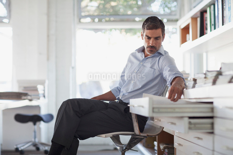 middle aged businessman opening drawer in officeの写真素材 [FYI02287127]