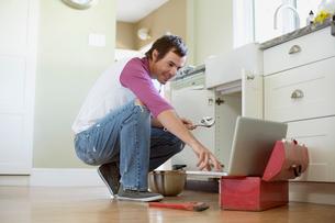 mid adult homeowner repairing plumbing under the sinkの写真素材 [FYI02287145]