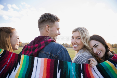 Portrait smiling friends wrapped in a blanketの写真素材 [FYI02287154]