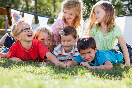 Cousins catching bubbles as they lie on the grass.の写真素材 [FYI02287260]
