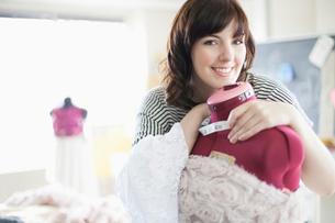 clothing designer smiling and hugging dress formの写真素材 [FYI02287262]