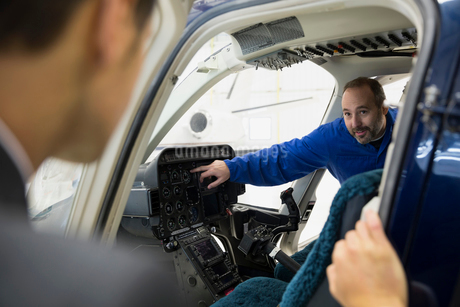 Mechanic explaining helicopter cockpit gauge to pilotの写真素材 [FYI02287277]