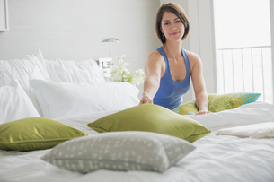 Mid-adult woman making bed in contemporary bedroom.の写真素材 [FYI02287294]