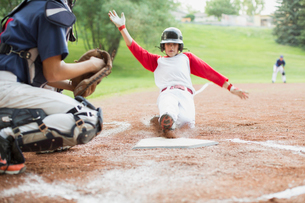 young male baseball player sliding into homeの写真素材 [FYI02287397]
