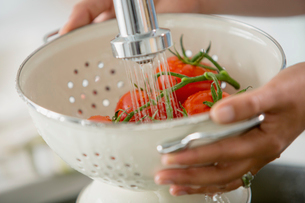 Woman rinsing tomatoes on the vine in colander.の写真素材 [FYI02287399]