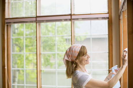 middle aged woman washing windows in homeの写真素材 [FYI02287445]