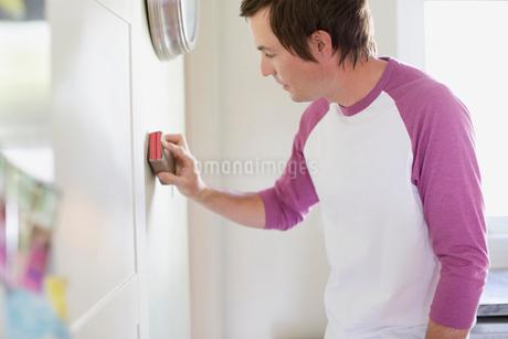 mid adult man sanding wall in kitchenの写真素材 [FYI02287453]