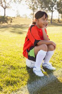 girl soccer player sitting on soccer ball on sidelinesの写真素材 [FYI02287454]