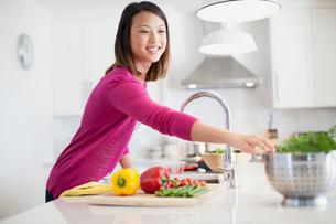 Happy young woman preparing food in kitchenの写真素材 [FYI02287508]