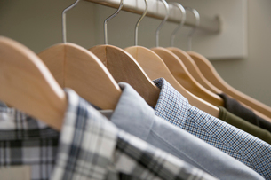 Close-up of mens shirts on wooden hangers.の写真素材 [FYI02287521]