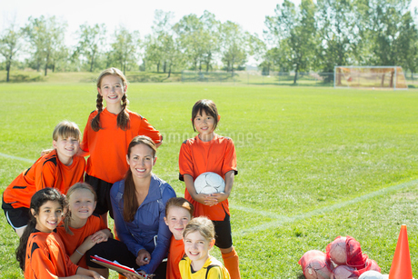 girls soccer team smiling with coachの写真素材 [FYI02287624]
