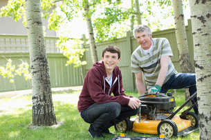 father and son maintaining lawn mowerの写真素材 [FYI02287667]