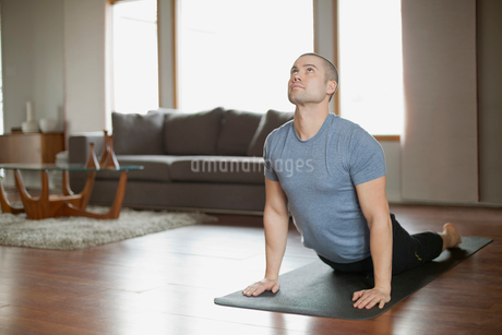 man doing yoga poses at homeの写真素材 [FYI02287742]