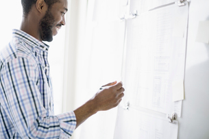 African american businessman reviewing plans on whiteboardの写真素材 [FYI02287762]
