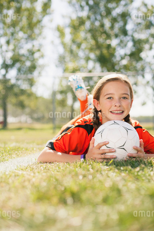 young female soccer player lying on grass with chin on soccer ballの写真素材 [FYI02287804]