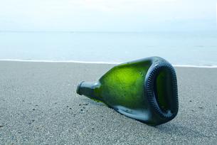 砂浜の光の当たった潰れた緑の瓶の写真素材 [FYI02287884]