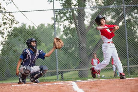 Young male baseball player swinging at baseball.の写真素材 [FYI02287985]