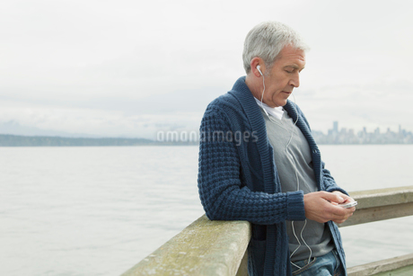 Middle-aged man listening to music by waterfront.の写真素材 [FYI02287999]