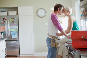 mid adult couple being affectionate in the kitchenの写真素材 [FYI02288006]