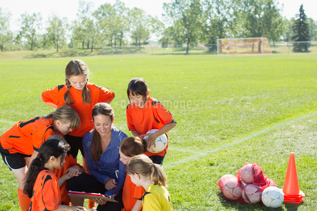 girls soccer team looking at playbook with coachの写真素材 [FYI02288145]