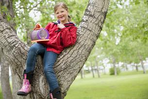 female elementary student sitting in treeの写真素材 [FYI02288173]