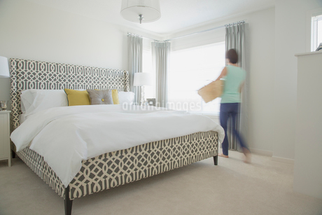 Woman with laundry basket in contemporary bedroom.の写真素材 [FYI02288242]