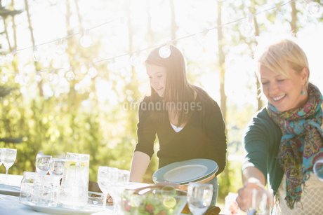 Mother and teenage daughter setting table outdoors.の写真素材 [FYI02288351]