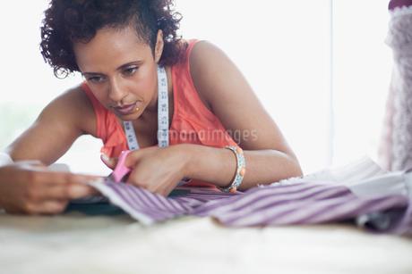dress designer cutting fabric in studioの写真素材 [FYI02288399]