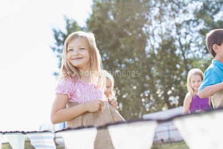 Cute, blond girl racing in potato sack race.の写真素材 [FYI02288443]