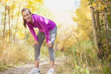Woman stopping to stretch during outdoor run.の写真素材 [FYI02288476]