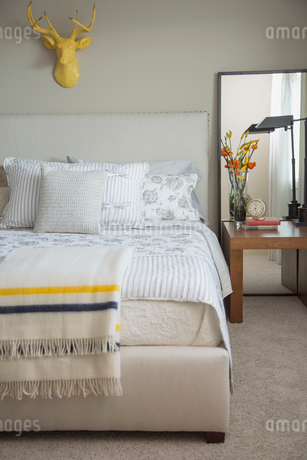 Contemporary bedroom with yellow deer head on wall.の写真素材 [FYI02288477]