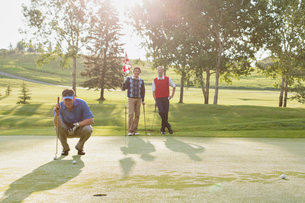 golfer focussed on putt while friends watchの写真素材 [FYI02288491]