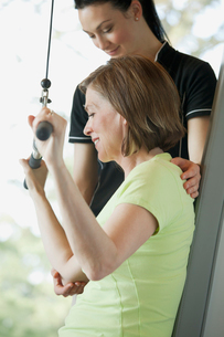 trainer assisting woman with weight trainingの写真素材 [FYI02288588]