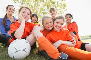 Girls soccer team sitting on grass together.の写真素材 [FYI02288606]