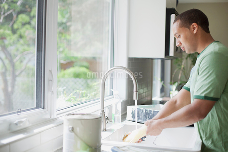 young adult man washing up paint rollerの写真素材 [FYI02288610]