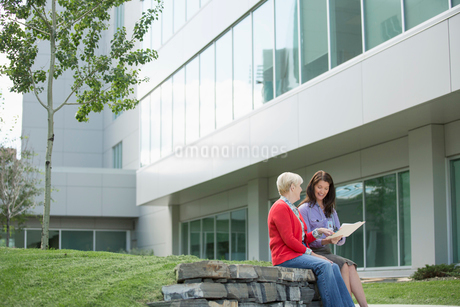 doctor sitting outdoors with senior womanの写真素材 [FYI02288628]