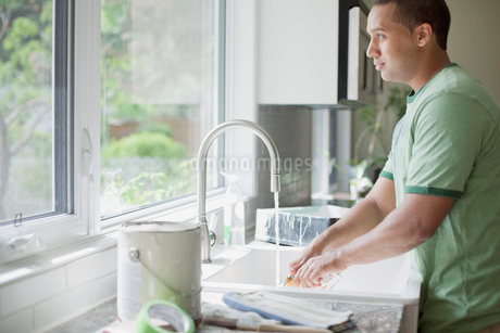 young adult man washing up painting toolsの写真素材 [FYI02288682]
