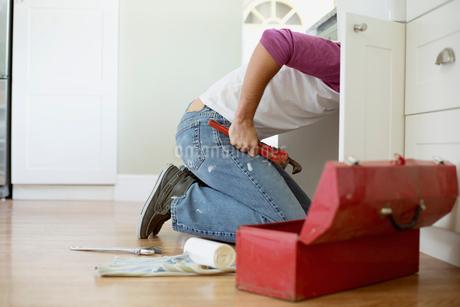 mid adult homeowner repairing plumbing under the sinkの写真素材 [FYI02288691]
