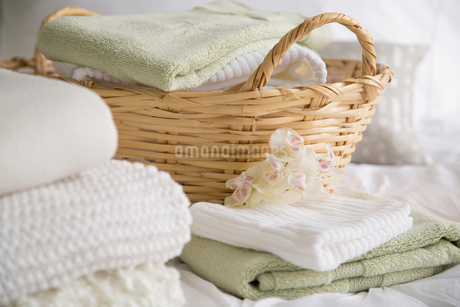 Folded towels and bedding in wicker basket.の写真素材 [FYI02288694]