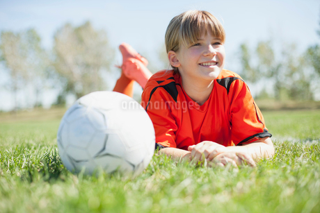 Girl soccer player lying on grass with soccerball.の写真素材 [FYI02288702]