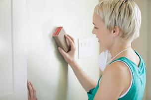 pretty, mid adult woman sanding wallの写真素材 [FYI02288745]