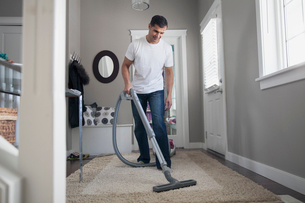 Man vacuuming rug at front entrance of homeの写真素材 [FYI02288760]